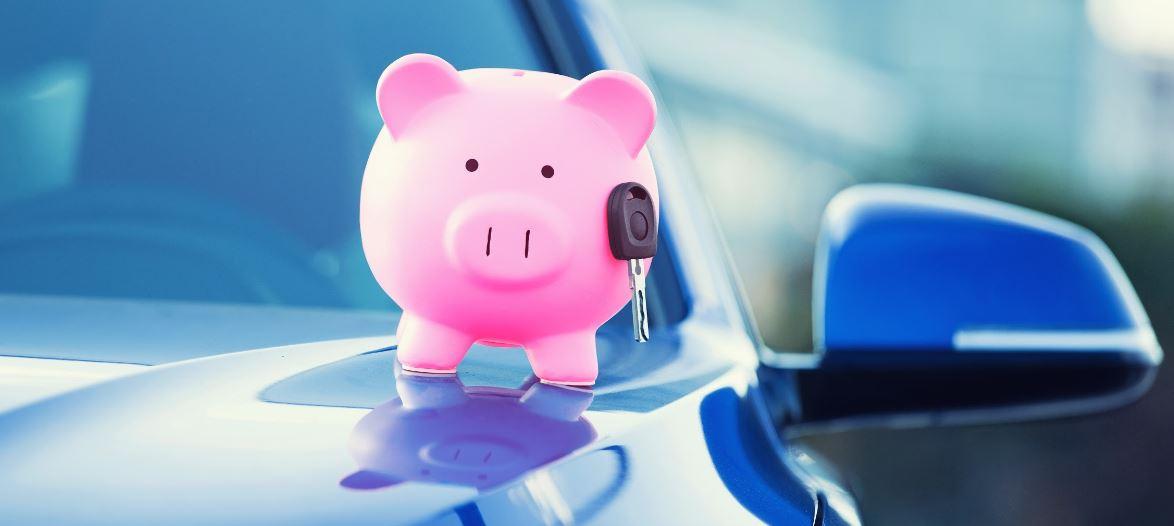 Pink piggy bank with a car key on hood